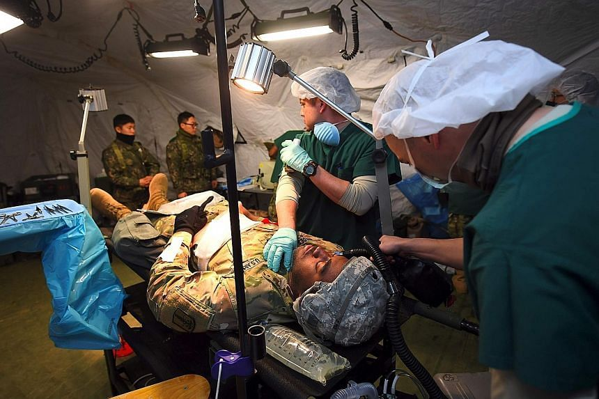 US medics during a joint mock evacuation as part of the annual military exercises known as Key Resolve and Foal Eagle at a South Korean Army hospital in Goyang, north-west of Seoul, yesterday. Pyongyang lobbed four ballistic missiles towards Japan la