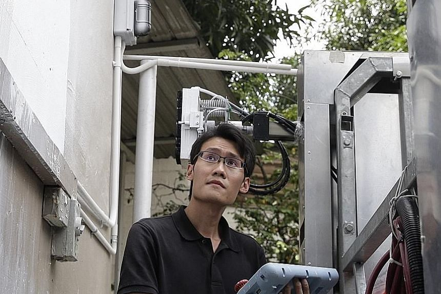 Mr Chee Keai Jiang, 27, a research staff member at NTU's Robotic Research Centre, controlling the arm of the OutoBot via a tablet. The locally built system was co-developed by Elid Technology International and NTU.