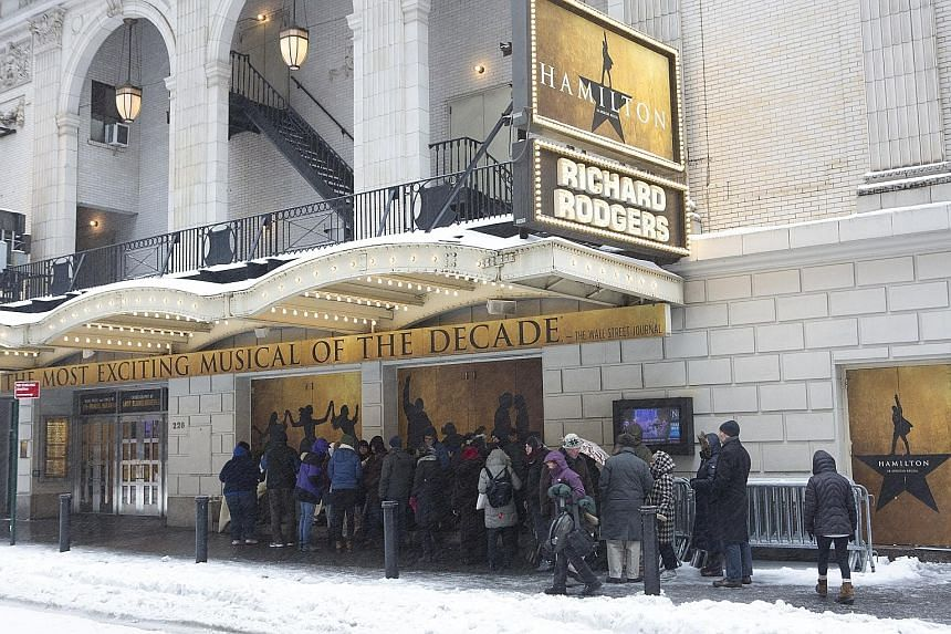 A line of people in New York on Tuesday, waiting for cancellation tickets to Broadway's Hamilton, a musical about the life of American founding father Alexander Hamilton. Expecting 0.6m of snow, New York City ended up with less than half that and lif