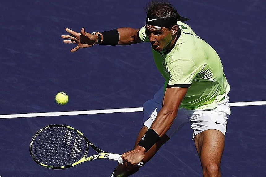 Rafael Nadal reaching for a backhand volley during his 6-3, 7-5 win against fellow Spaniard Fernando Verdasco in the third round of the ATP Indian Wells Masters on Tuesday. Despite losing his last two matches against Roger Federer, Nadal leads the Sw