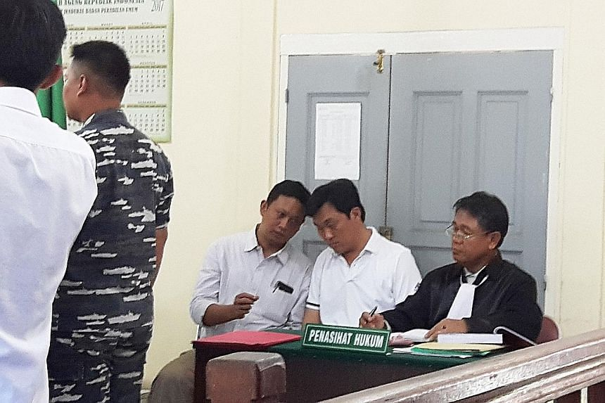 Tan (middle) listens as an interpreter briefs him. Beside him is his lawyer. Tan has been in the custody of the Indonesian navy since his arrest on Aug 20 last year.