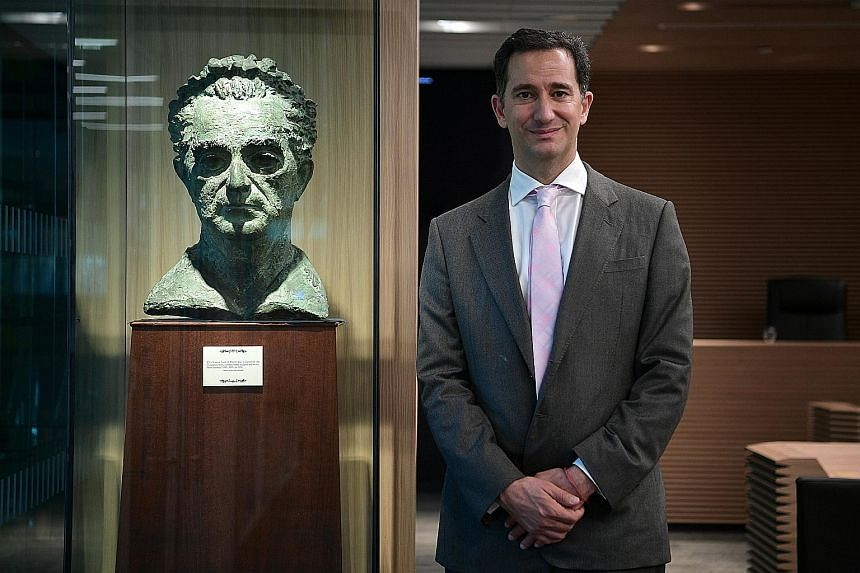 Dr Marshall at SMU's moot court with the bust of Mr Marshall, which is on loan to the university. The bust has been in the family since 1956, when it was sculpted by a London-based artist.