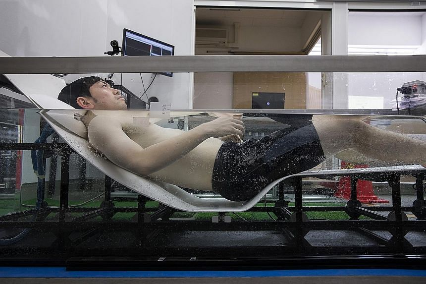 A researcher wearing active marker motion sensors and electrodes to evaluate the electrical acitivity in his brain, while conducting bathing tests inside the bathroom laboratory at the Toto's research and development centre in Chigasaki, Kanagawa, Ja