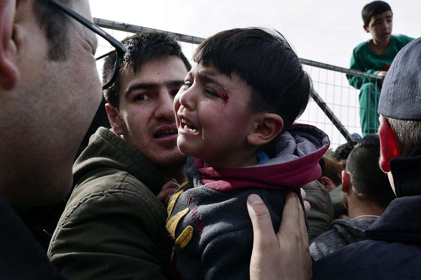 An injured boy cries as police face angry migrants blocking entry to the Hellinikon camp in Athens in protest at poor living conditions.