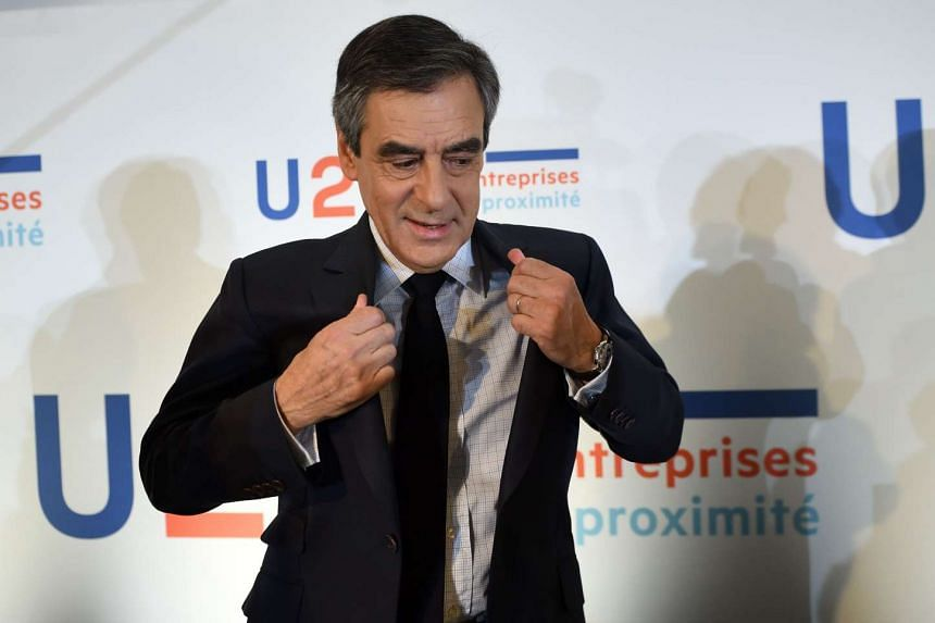 Fillon adjusts his jacket as he leaves after a press conference as part of his campaign, on March 16, 2017 in Paris.