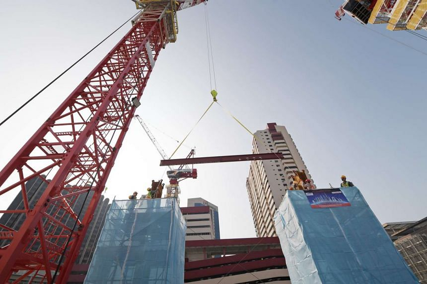 The first beam of the superstructure is hoisted in place at the launch of the superstructure of the new State Courts Towers on March 17, 2017.