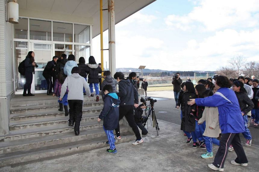 Local residents move towards a school gymnasium during an evacuation drill at Oga city, Akita prefecture on March 17, 2017.