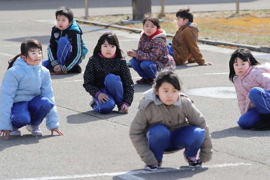 Elementary school students participate in an evacuation drill for local residents based on the scenario that a ballistic missile launched landed in Japanese waters on March 17, 2017.