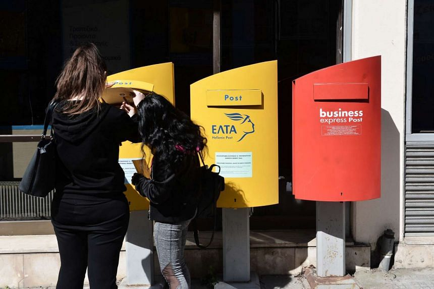 A woman posts a letter in a mailbox outside of a post-office in Thessaloniki on March 17, 2017. Two letters bombs were posted from Greece, one of which exploded at the IMF offices in Paris.