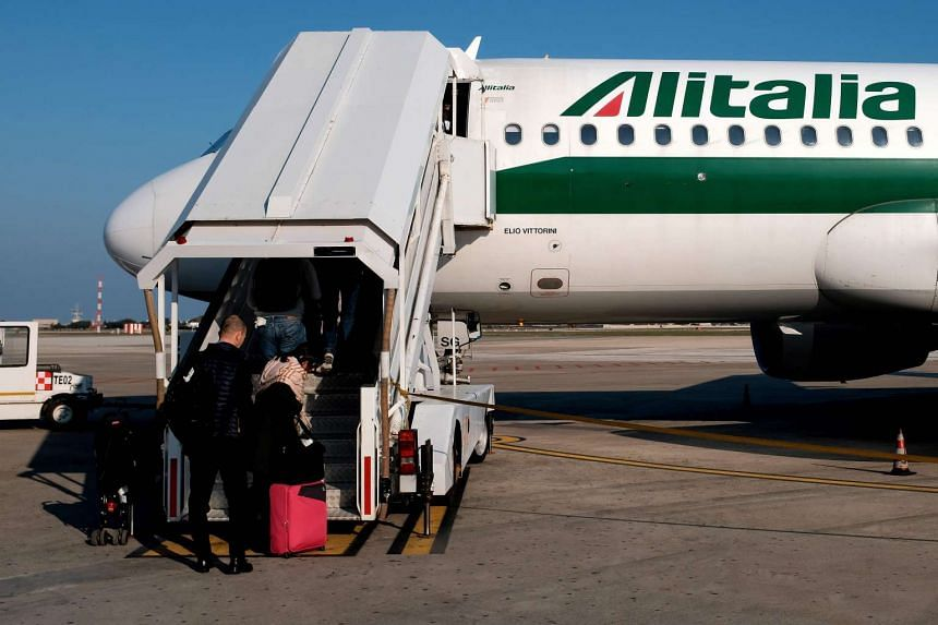 A picture taken on March 15, 2017, shows passengers boarding an Alitalia - Etihad plane on the runway of the airport of Brindisi.