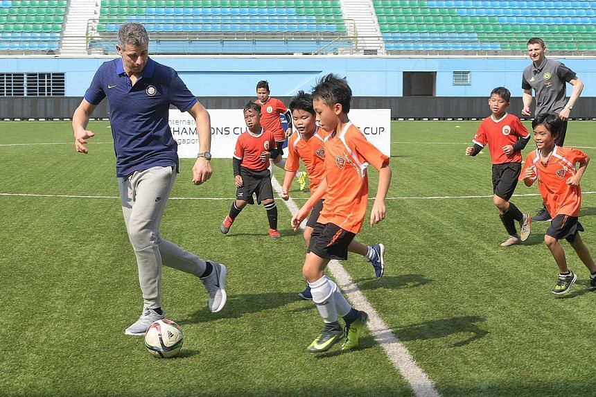 Former Inter Milan goalkeeper Francesco Toldo (left) and former Chelsea striker Tore Andre Flo (right) in a kickabout with children from local football training centres at Jalan Besar Stadium yesterday.