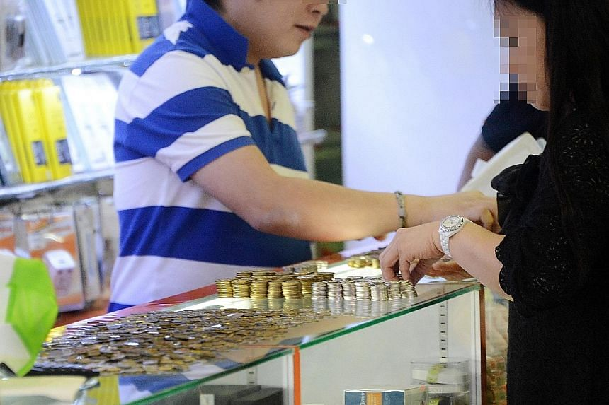 Above: Ms Zhou counting the coins she was given by a mobile phone shop in Sim Lim Square, which had been ordered to refund her $1,000 as well as a $10 administrative fee, in October 2014. Right: An employee of car dealer Exotic Motors collecting the
