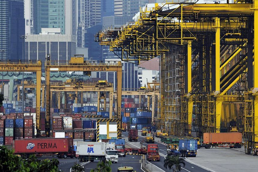 Shipping containers are moved and stacked at a port in Singapore.