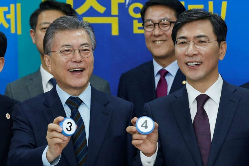 Democratic Party's candidates for the presidential primary Moon Jae In (Left) and Ahn Hee Jung pose with their elective symbol numbers at an event to declare their fair contest in the party's presidential primary in Seoul, South Korea, on March 14, 2