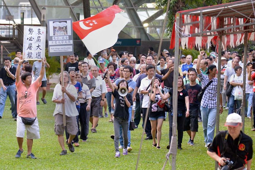 Han Hui Hui (with loudspeaker) and Roy Ngerng (carrying state flag) with supporters at Hong Lim Park, on Sept 27, 2014.
