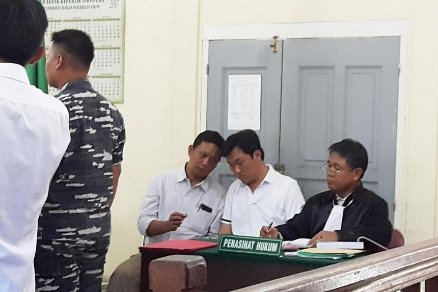 Ricky Tan Poh Hui (middle), a Singaporean boat captain, listening as an interpreter briefs him.