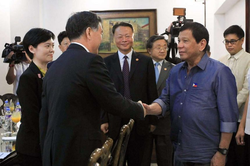 This handout photo taken and released on March 17, 2017, by the Presidential Photographers Division (PPD) shows Philippine President Rodrigo Duterte (Right) shaking hands with Chinese Vice-Premiere Wang Yang  during a courtesy call at the presidentia