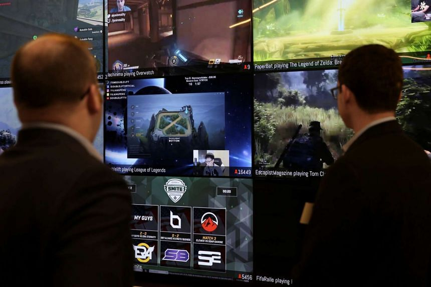 Men look at a wall of real-time video game play.