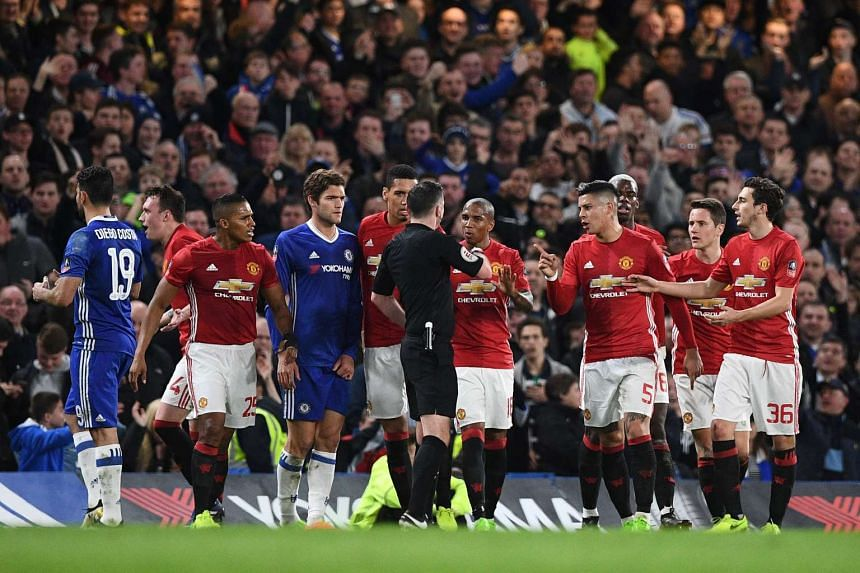 English referee Michael Oliver (centre) speaks with Manchester United players after showing a red card for a second bookable offence, during the English FA Cup quarter final football match.