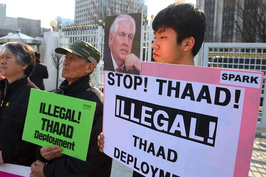 South Korea's anti-war activists hold placards during a rally against the planned deployment of the US-built Terminal High Altitude Area Defense (THAAD) anti-ballistic missile system, outside the government complex in Seoul on March 17, 2017.