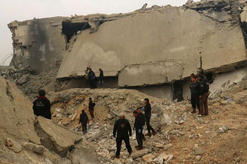 Civil defence workers and others inspect a damaged building in Syria after an airstrike on March 17, 2017.