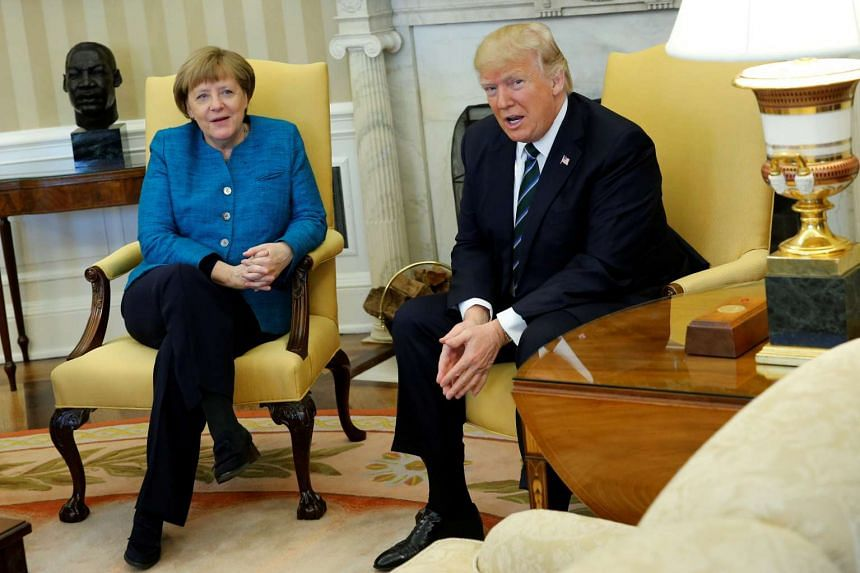 Donald Trump and Angela Merkel watch as reporters enter the room before their meeting in the Oval Office.