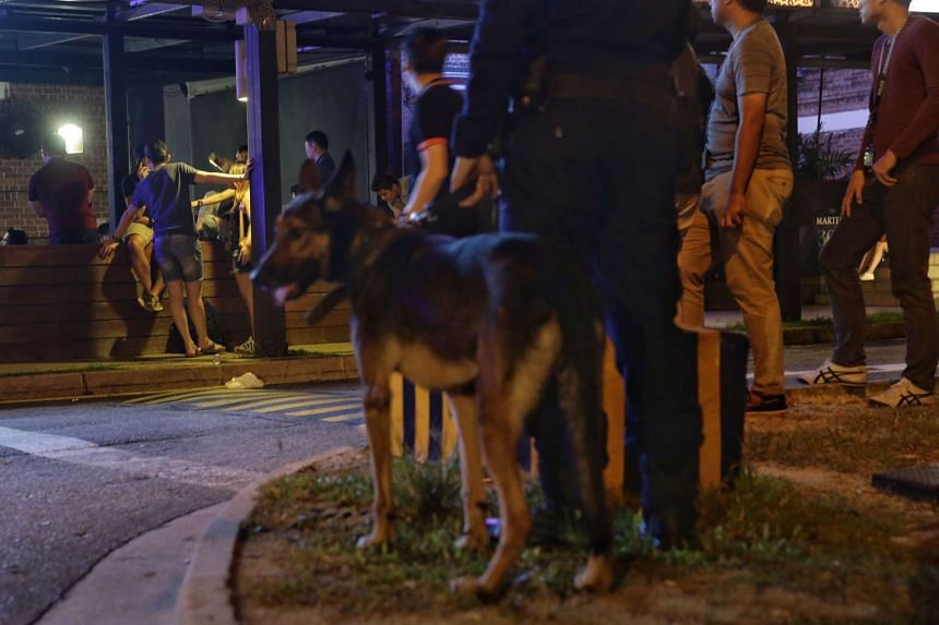 A Special Operations Command officer with a dog stands by as the police check a club in the wee hours of Saturday (March 18).