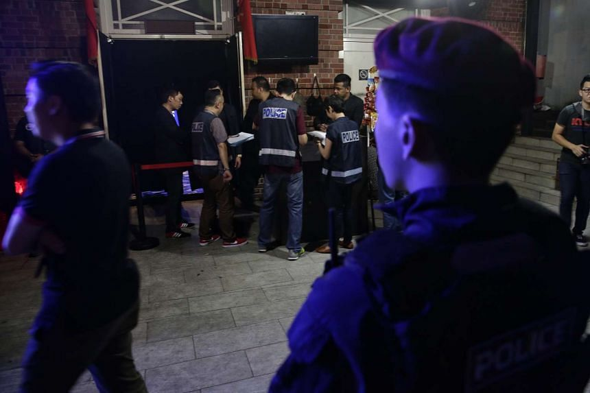 Police checking a club's security officers' passes and whether its staff are registered in the wee hours of Saturday (March 18).