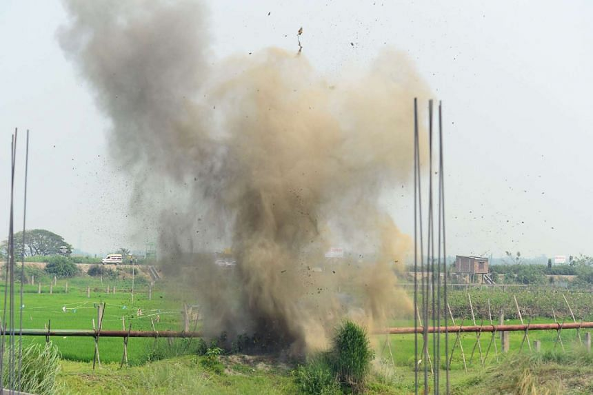 Explosives recovered from a foiled attacker is blown up by a Bangladeshi police bomb disposal unit in a field on the outskirts of Dhaka on March 18, 2017.