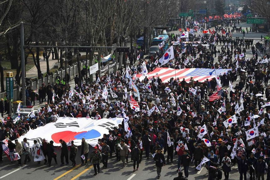 Supporters of South Korea's impeached ex-president Park Geun-Hye carry huge flags of South Korea and the US as they march toward the Constitutional Court during a rally demanding a repeal of the impeachment in Seoul on March 18, 2017.