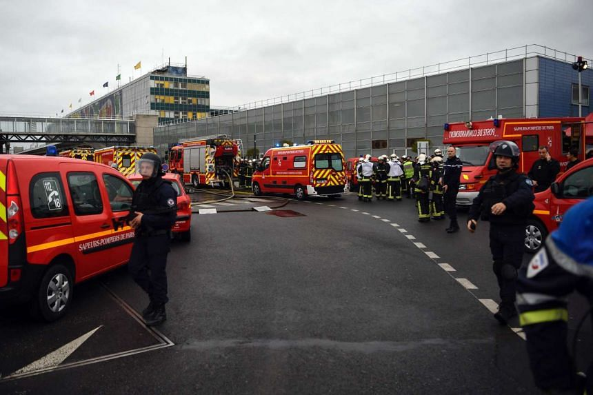 French policemen and firefighters secure the area at Paris' Orly airport on March 18, 2017 following the shooting of a man by French security forces.