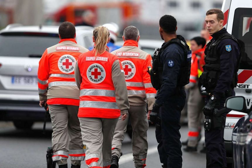 French Red Cross workers arrive at Paris' Orly airport on March 18, 2017 following the shooting of a man by French security forces.