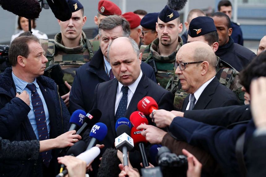 French Interior Minister Bruno Le Roux (centre) speaks to the press next to French Defence Minister Jean-Yves Le Drian (right) on March 18, 2017 at Paris' Orly airport following the shooting of a man by French security forces after tried to grab a so