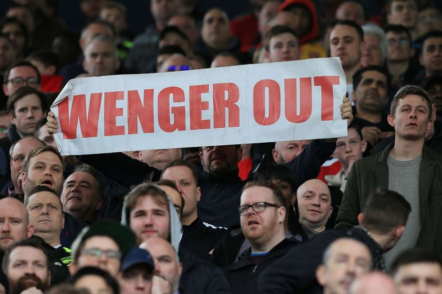 A fan holds up an anti-Arsene Wenger sign during the match.