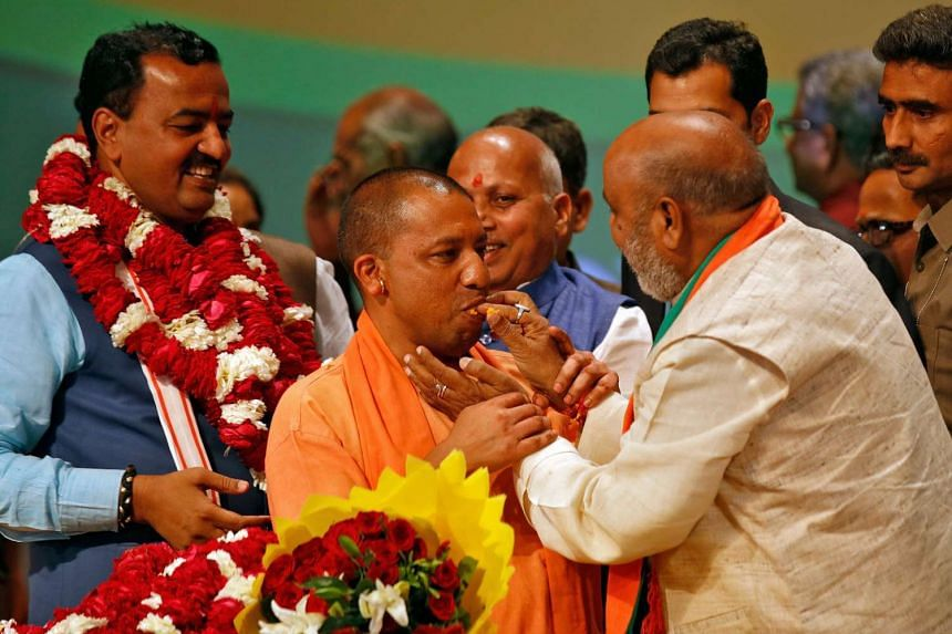 India's ruling Bharatiya Janata Party (BJP) leader Yogi Adityanath (centre) is offered sweets after he was elected as Chief Minister of India's most populous state of Uttar Pradesh, during the party lawmakers' meeting in Lucknow, India on March 18, 2