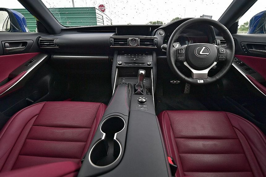 The Lexus IS Turbo is capable of manic manoeuvres with menacing-looking headlamps to match. Inside (below), the infotainment screen and the compartment on the centre armrest have been enlarged.