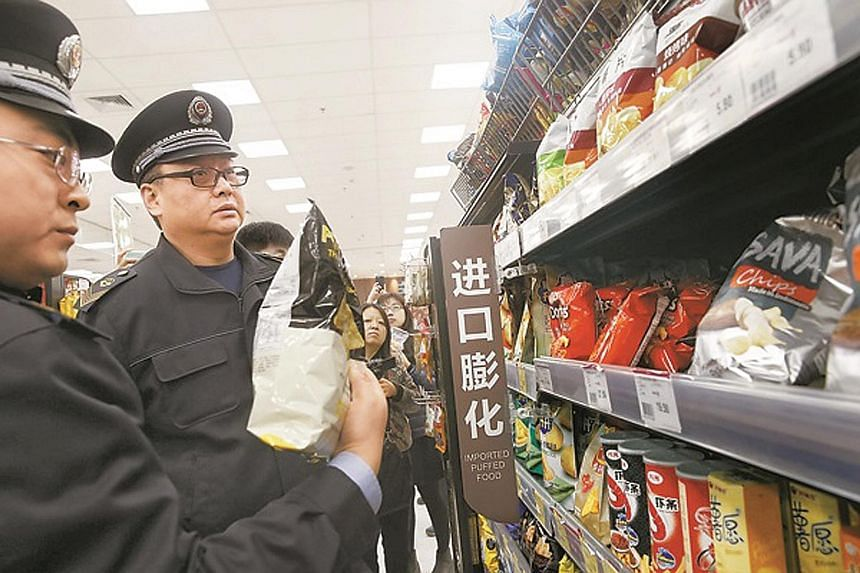 Officers from the Beijing Food and Drug Administration checking imported food at a supermarket on Thursday. In Beijing, major supermarkets and e-commerce platforms have started inspections following the CCTV report accusing Muji of selling contaminat