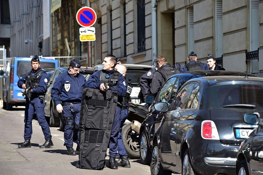 Police officers securing the area near the Paris offices of the International Monetary Fund on Thursday (March 16) after a letter bomb exploded in the premises.