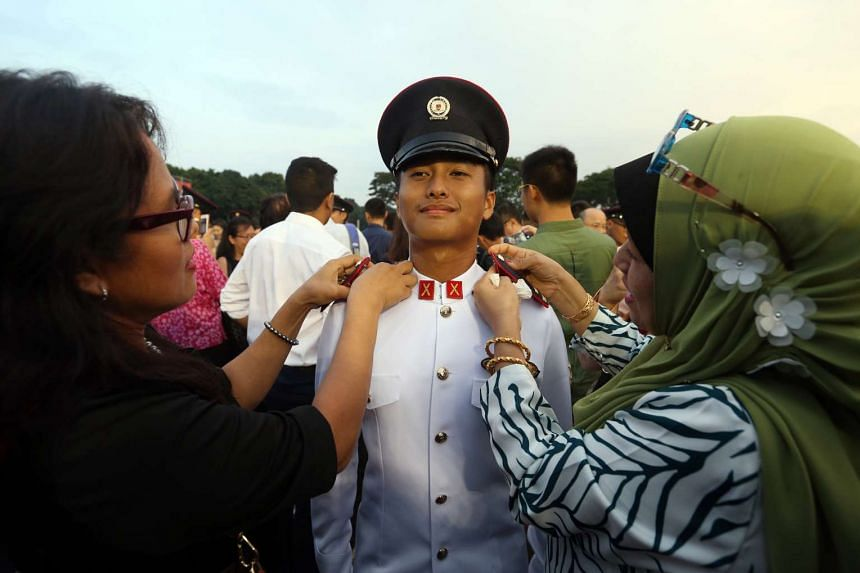 Second Lieutenant Mohamed Izzmel Sufyan Mohamed smiling as his mother Azidah Amri (left) and relative Ruzaima Amri affix his epaulettes at the Officer Commissioning Parade on March 18, 2017.