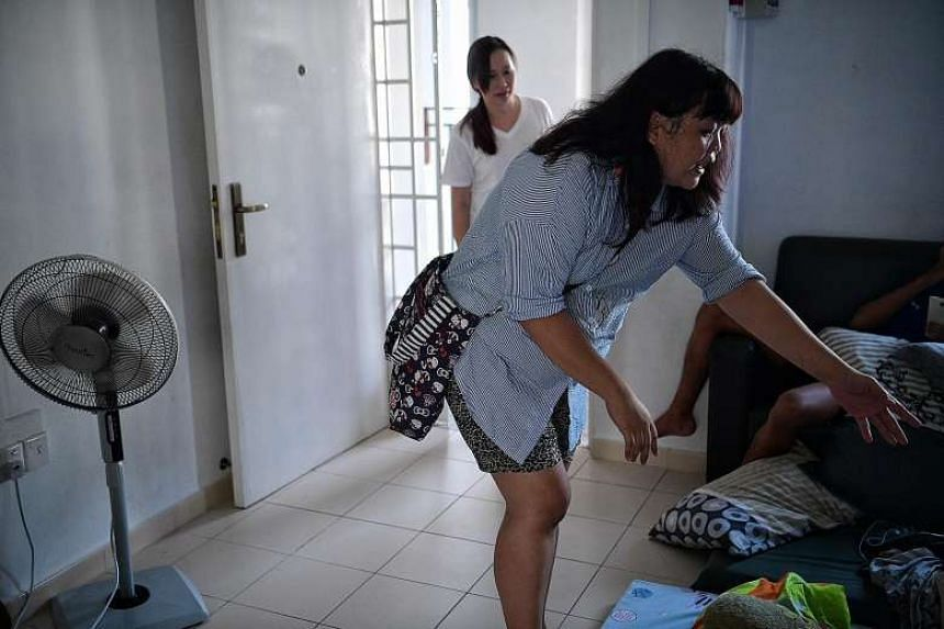 Infant-care teacher Priscilla Ong and her son, Zechariah (above), 16, deliver groceries to a needy household in Yishun. Ms Ong's outreach to children at her centre has turned into a full-fledged community effort called Project Love Lunch, which distr