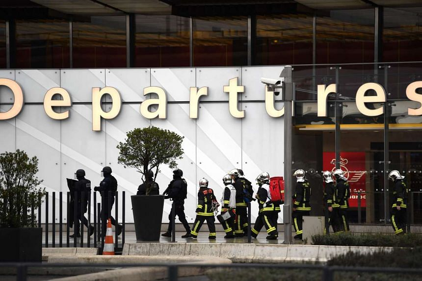 French firefighters and RAID police unit officers secure Paris' Orly airport on March 18, 2017, following the shooting of a man by French security forces.