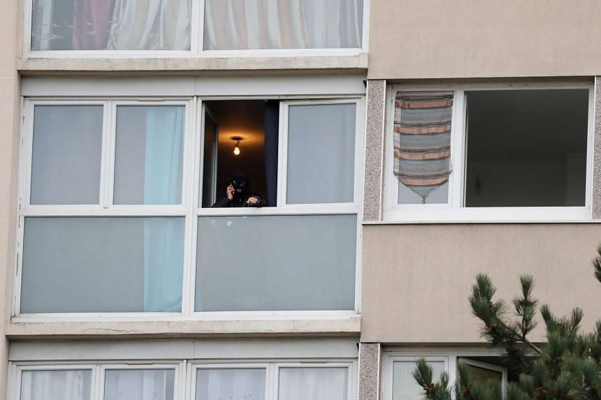 A police officer uses his mobile phone at the house of the suspect of an attack at the Paris Orly's airport, on March 18, 2017 in Garges-les-Gonesse.
