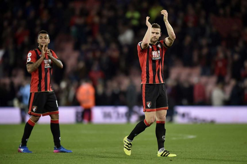 Bournemouth's Joshua King and Simon Francis applaud fans after the game.