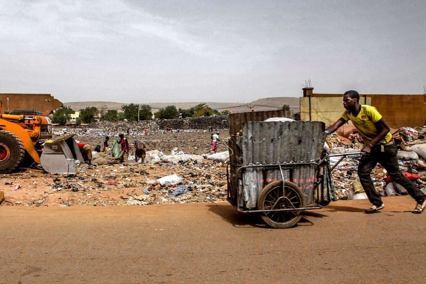This file photo taken on March 08, 2017 shows a garbage scavenger pushing a cart through a dump in Bamako.