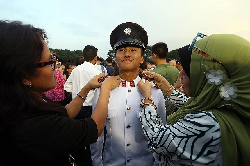 Second-Lieutenant Mohamed Izzmel having his epaulettes attached by his mother, Madam Azidah Amri (left), and his aunt, Madam Ruzaima Amri, at Safti Military Institute yesterday.