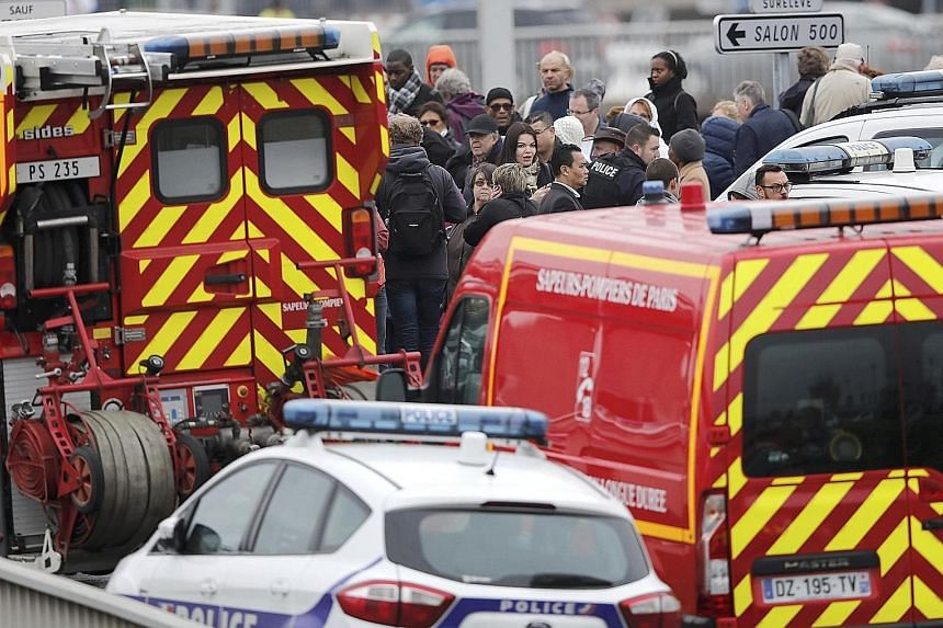 From top: A woman being kept warm under a rescue blanket was among the thousands who were forced to evacuate the Orly-Sud terminal after the shoot-out yesterday. Emergency workers rushed in to provide medical assistance, even as stranded passengers w