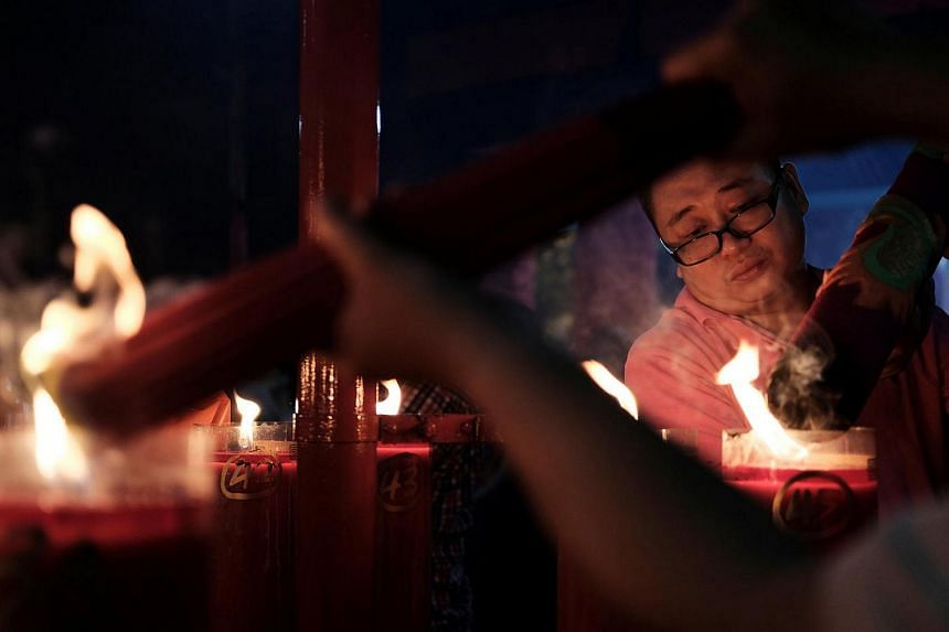 A man lights up incense at Dharma Sakti temple before praying during the Chinese Lunar New Year, in Jakarta, Indonesia.