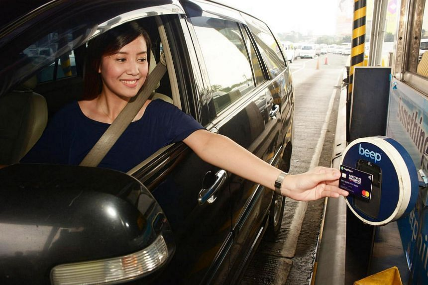 """A motorist pays toll at the North Luzon Expressway with a PayMaya-issued card. PayMaya offers a smartphone app that allows users to create a """"virtual"""" credit card, without needing a bank account."""