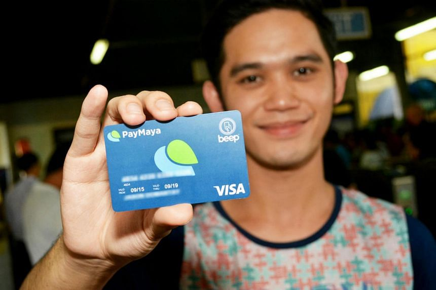 "A user shows his PayMaya-issued card. PayMaya offers a smartphone app that allows users to create a ""virtual"" credit card without needing a bank account."