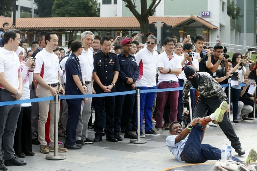 Prime Minister Lee Hsien Loong looks on as a simulated terror attack is being carried out during the Emergency Preparedness Day at Teck Ghee constituency on Sunday (March 19).